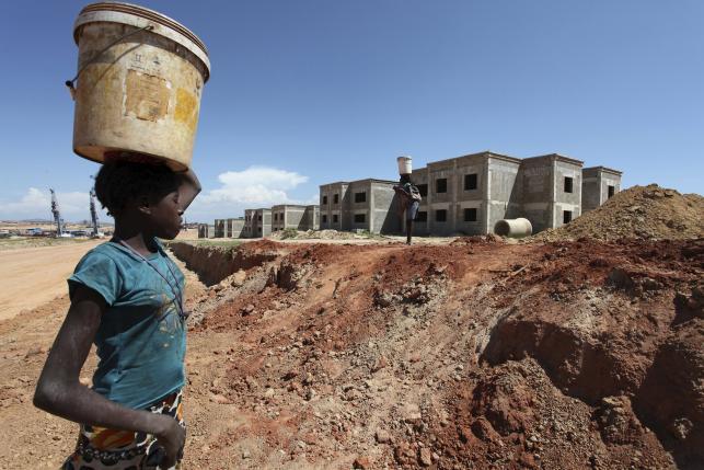 A woman walks past a Chinese construction site in Lubango, Angola, March 5, 2014.  REUTERS/Herculano Coroado