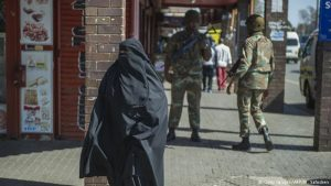 Muslim woman in Hijab walks past soldiers in Johannesburg SA